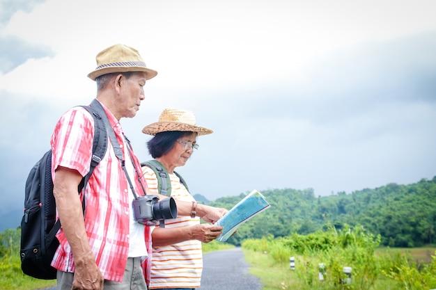 Le coppie asiatiche anziane viaggiano nella foresta, portando una mappa per studiare il percorso.