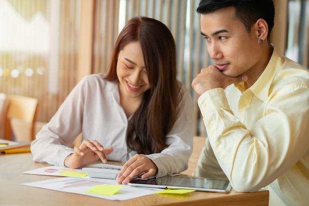 Le coppie asiatiche calcolano le entrate e le spese per tagliare le spese non necessarie e stanno pianificando di prendere in prestito denaro per acquistare una nuova casa. concetti per la pianificazione degli investimenti e la pianificazione finanziaria per la famiglia
