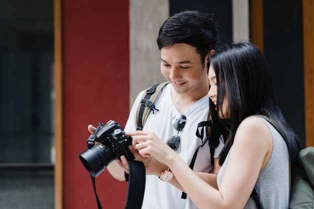 Le coppie asiatiche del viaggiatore che per mezzo della macchina fotografica per prendono un'immagine mentre passano il viaggio di festa a pechino, cina