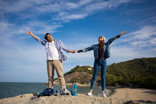 Le coppie asiatiche in camicia blu con la tazza di caffè e la macchina fotografica d'annata fanno un picnic sulla montagna vicino alla vista del mare della spiaggia felice e sorridono affronta