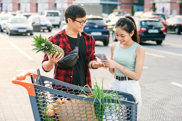 Le coppie asiatiche sorridenti che stanno carrello vicino, l'uomo tiene l'ananas e la donna allegra conta le banconote