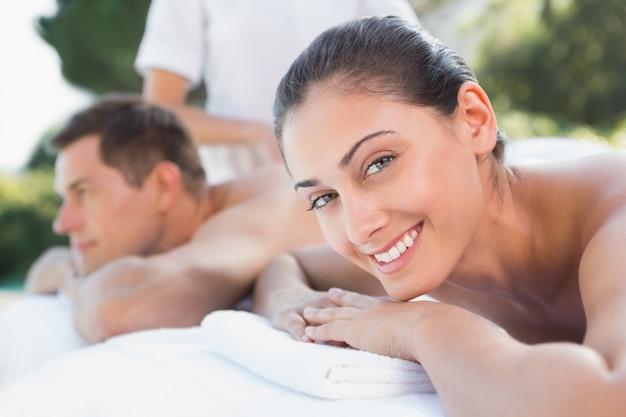 Le coppie attraenti che godono delle coppie massaggiano il poolside