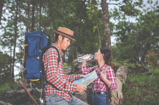 Le coppie bevono acqua e vedono una mappa nella foresta tropicale insieme a zaini nella foresta. avventura, viaggio, arrampicata, escursione.