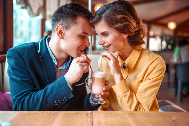 Le coppie bevono un cocktail insieme dalle cannucce