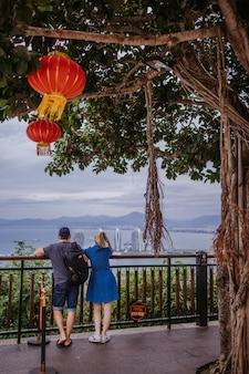 Le coppie caucasiche di viaggio in cina viaggiano con le lanterne rosse cinesi nel parco naturale per il fondo lunare dell'insegna di celebrazione cinese del nuovo anno.