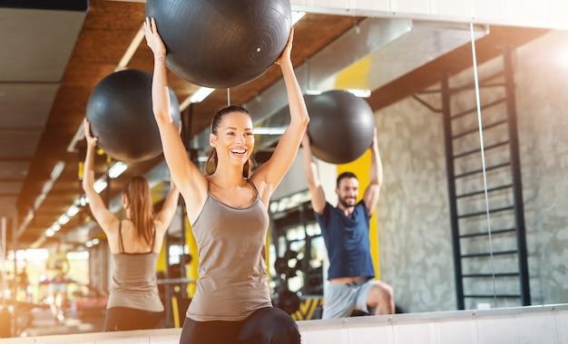 Le coppie caucasiche felici sorridenti in abiti sportivi che fanno i pilates si esercitano in palestra.