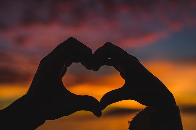 Le coppie che fanno il cuore modellano dalle mani sulla riva di mare