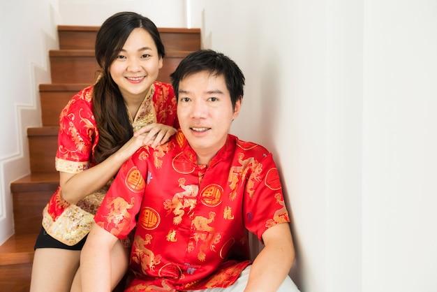 Le coppie cinesi vestono il costume rosso del cheongsam in casa