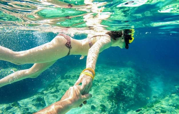 Le coppie della presa d'aria che nuotano insieme nel mare tropicale con seguono la composizione