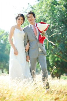 Le coppie della sposa e dello sposo che si levano in piedi sopra il campo dei prati