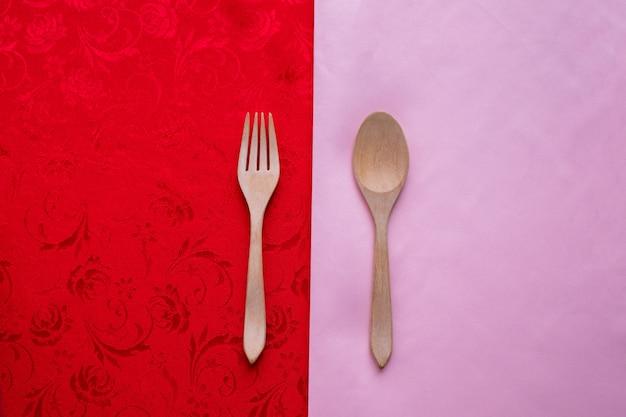 Le coppie di amore, il cucchiaio, forchetta sul fondo rosa e rosso di struttura della tovaglia.