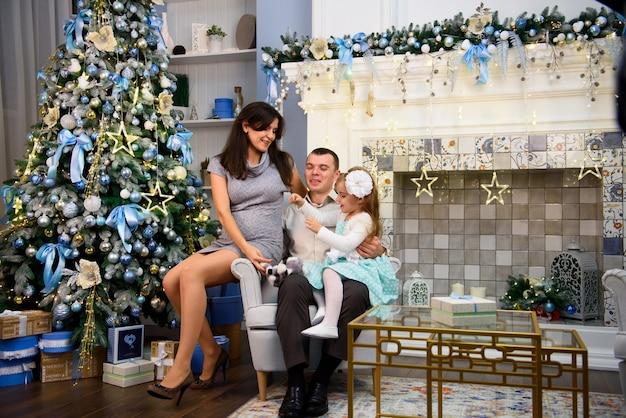 Le coppie di famiglia felici fanno regali nel soggiorno, dietro l'albero di natale decorato, la luce dona un'atmosfera accogliente.
