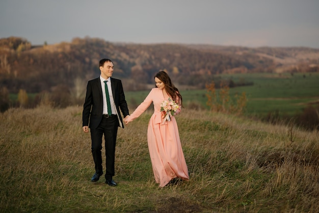 Le coppie di felicità camminano al giorno delle nozze, sullo sfondo di una splendida vista della natura al tramonto
