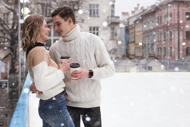 Le coppie di giovani coppie nell'amore datano alla pista di pattinaggio nevica bevendo il cacao