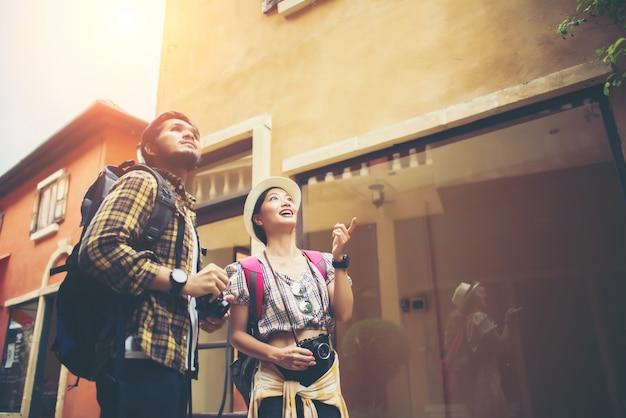 Le coppie di giovani turisti che camminano in urbano godono della festa insieme. concetto di viaggio di coppia.