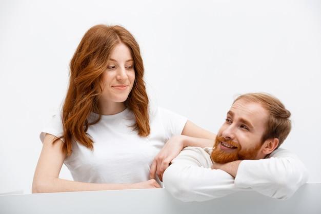 Le coppie divertenti della testarossa si appoggiano la tavola