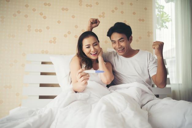Le coppie felici che sorridono dopo scoprono il test di gravidanza positivo in camera da letto