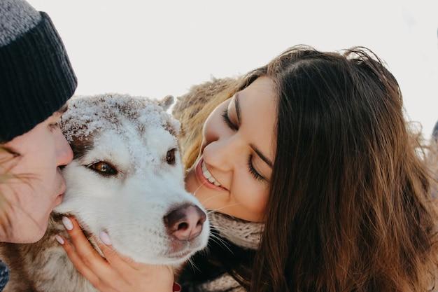 Le coppie felici con il cane haski al parco naturale della foresta nella stagione fredda. viaggi avventura storia d'amore