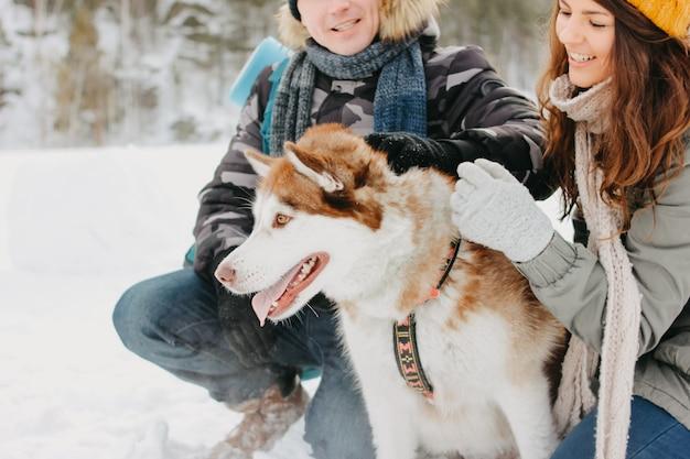 Le coppie felici con il cane haski al parco naturale della foresta nella stagione fredda