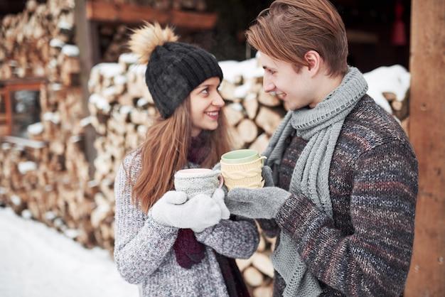 Le coppie felici di natale nell'amore abbracciano nella foresta fredda dell'inverno nevoso, copiano lo spazio, la celebrazione della festa del nuovo anno, le vacanze e le vacanze, il viaggio, l'amore e le relazioni