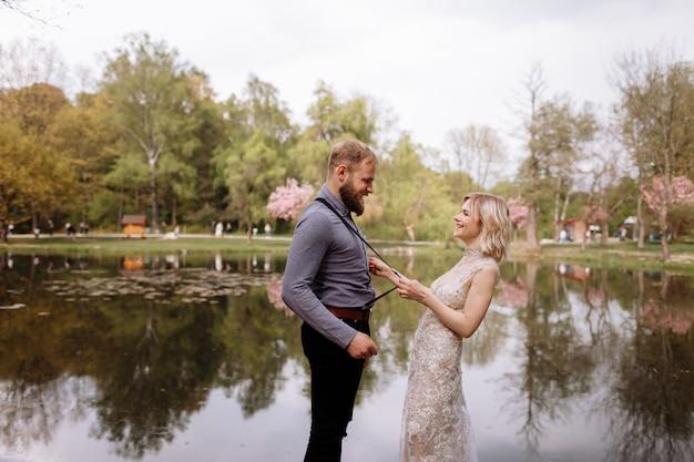 Le coppie felici di nozze si stanno divertendo nel parco sbocciante di sakura di primavera. donna in abito di lusso tirando barbuto mans bretelle vicino al lago. coppia di sposi nel parco. novelli sposi. matrimonio rustico.