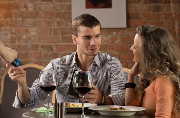Le coppie felici in ristorante pagano il loro pasto