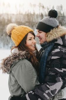 Le coppie felici nell'amore al parco naturale della foresta nella stagione fredda