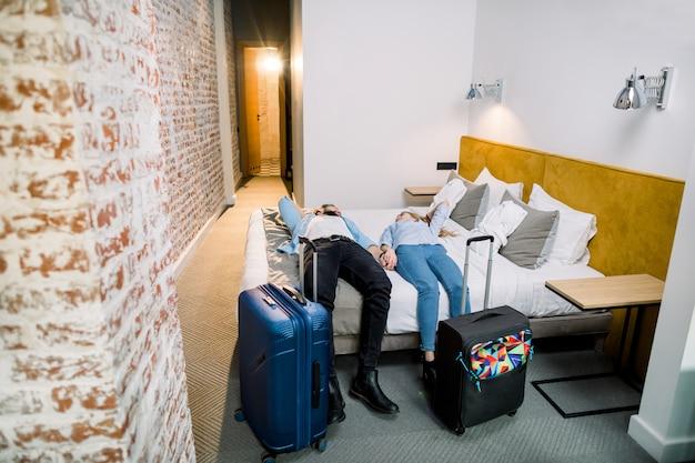 Le coppie felici nella camera di albergo moderna, festeggiano il concetto di viaggio. vista dall'alto di sorridente uomo e donna sdraiata sul letto