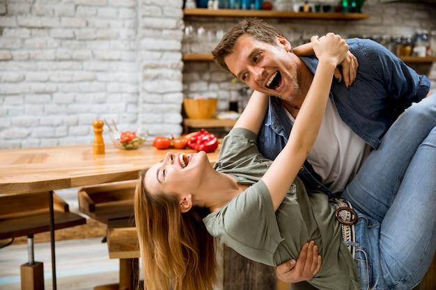 Le coppie felici si godono nella cucina moderna mentre la donna della tenuta dell'uomo sulle mani