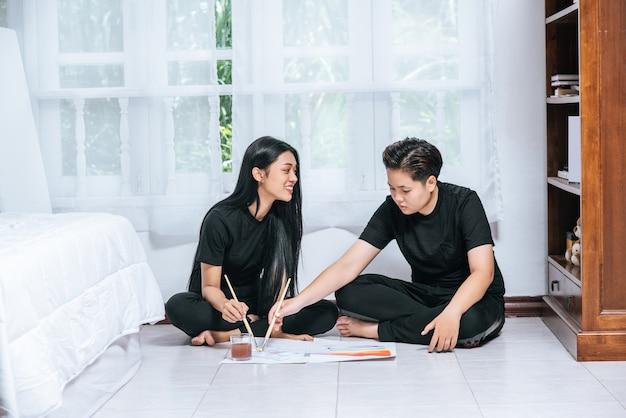 Le coppie femminili disegnano e dipingono su carta.