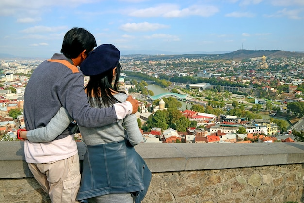 Le coppie godono della vista mozzafiato della città di tbilisi dalla fortezza antica di narikala, in georgia