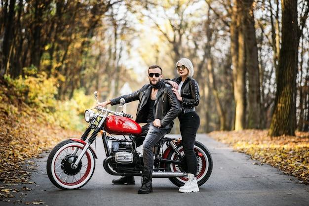 Le coppie graziose si avvicinano al motociclo rosso sulla strada nella foresta