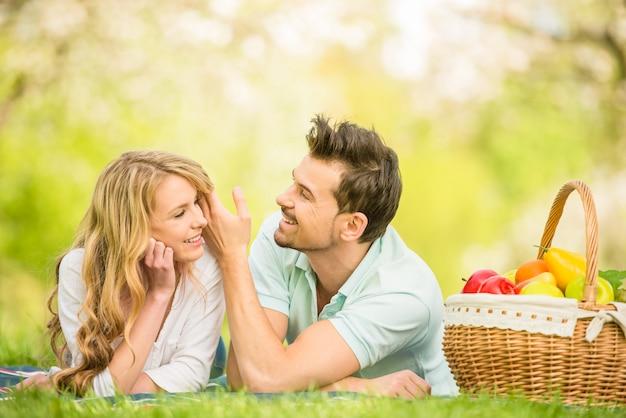 Le coppie hanno vestito la menzogne casuale sul prato inglese nel parco dell'estate.