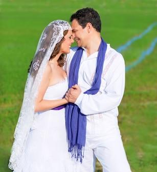 Le coppie in giorno delle nozze abbracciano in prato verde