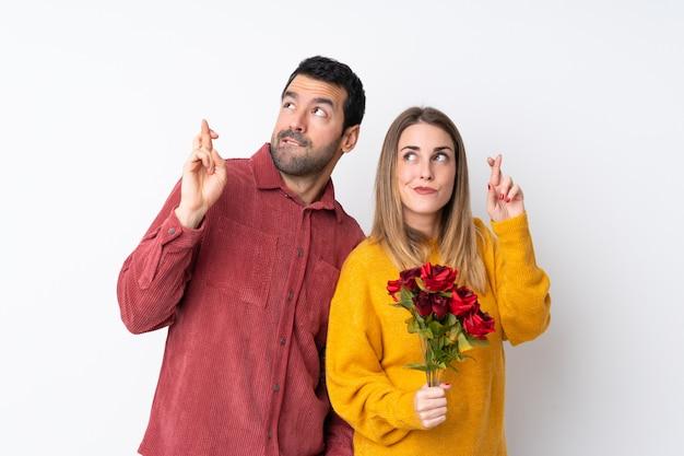 Le coppie in valentine day che tengono i fiori sopra la parete isolata con le dita che attraversano e che desiderano il meglio