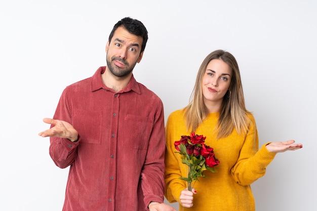 Le coppie in valentine day che tengono i fiori sopra la parete isolata sono infelici e frustrate con qualcosa perché non capiscono qualcosa