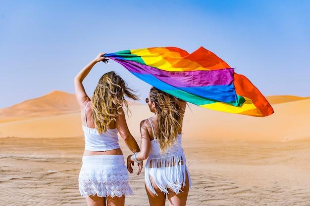 Le coppie lesbiche con i capelli biondi sono innamorate e felici camminano attraverso la sabbia del deserto durante le loro vacanze portando una bandiera arcobaleno che tengono con le mani e svolazzano nel vento nel giorno dell'orgoglio gay