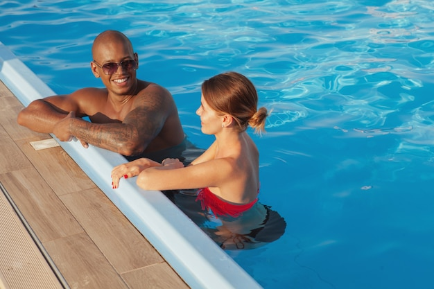 Le coppie multietniche felici che si rilassano nella piscina insieme, copiano lo spazio. uomo africano attraente e la sua ragazza che godono le vacanze estive al centro balneare