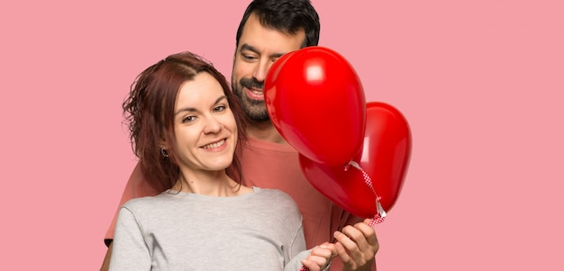 Le coppie nel giorno di s. valentino con i palloni con cuore modellano sopra fondo rosa isolato