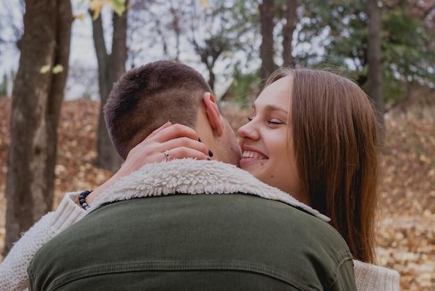 Le coppie nell'amore stanno sulle foglie cadute autunno in un parco, godendo di una bella giornata di autunno. l'uomo abbraccia la ragazza