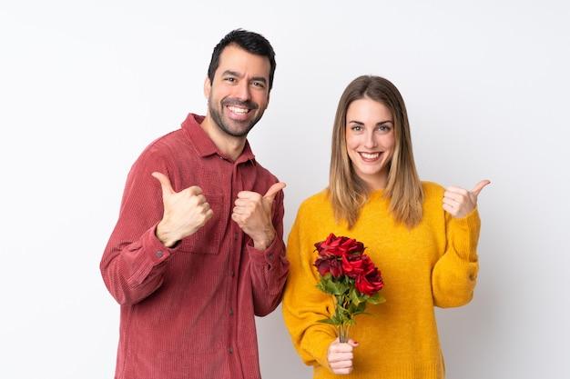 Le coppie nella tenuta di valentine day fioriscono sopra la parete isolata che dà un pollice in su gesto con entrambe le mani e sorridere