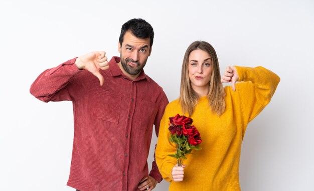 Le coppie nella tenuta di valentine day fioriscono sopra la parete isolata che mostra il pollice giù con entrambe le mani
