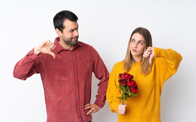 Le coppie nella tenuta di valentine day fioriscono sopra la parete isolata che mostra il pollice giù firma con l'espressione negativa