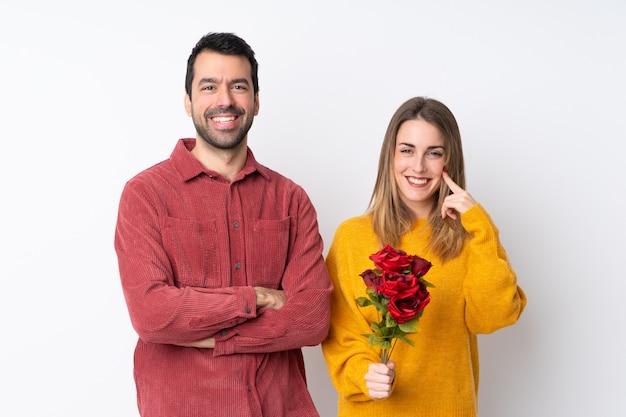 Le coppie nella tenuta di valentine day fioriscono sopra la parete isolata che sorridono con un'espressione dolce
