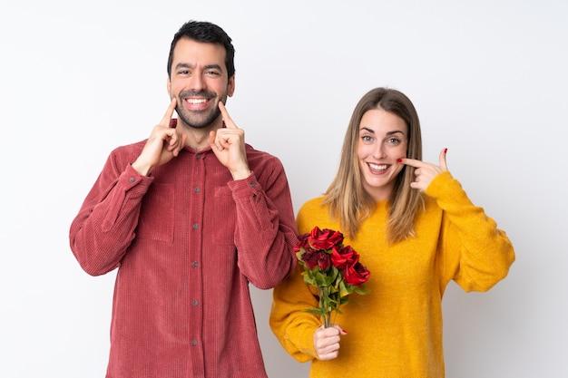 Le coppie nella tenuta di valentine day fioriscono sopra la parete isolata che sorridono con un'espressione felice e piacevole
