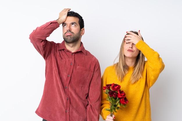 Le coppie nella tenuta di valentine day fioriscono sopra la parete isolata con espressione facciale sorpresa e colpita