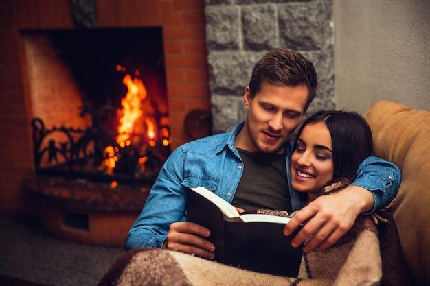 Le coppie positive e allegre si siedono insieme. giovane donna coperta di coperta. guy ha letto il libro per lei. si siedono vicino al camino.
