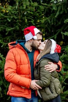 Le coppie romantiche in cappelli di natale si avvicinano all'albero di abete.