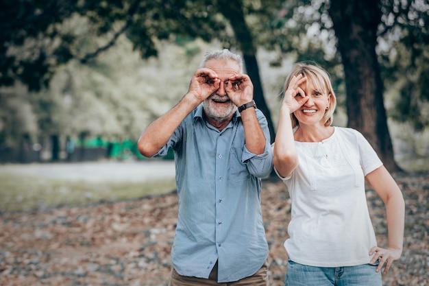 Le coppie senior con la mano giusta firmano il gesto sull'occhio nel parco, fondo della natura