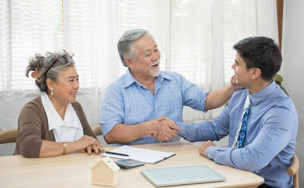 Le coppie senior soddisfatte sorridenti che fanno l'acquisto di vendita trattano il contratto di conclusione dall'agente immobiliare, la famiglia più anziana felice e il mediatore stringono le mani acconsentendo ad acquistare la nuova casa alla riunione.